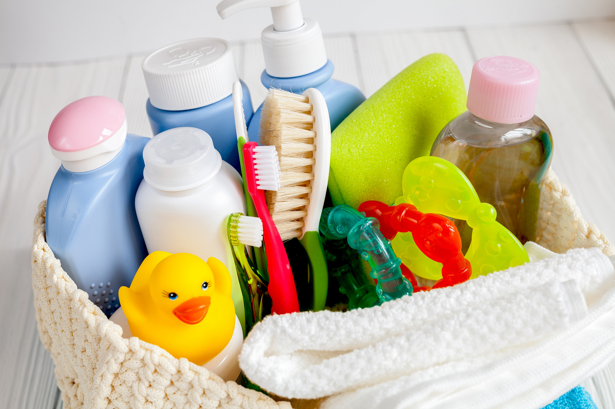 Various commodities in a basket (shampoo, toothbrush, toys)